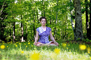 Woman is meditating on grass