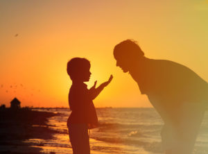 Father teaches son on beach