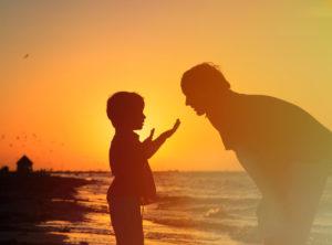 Father teaches son on beach